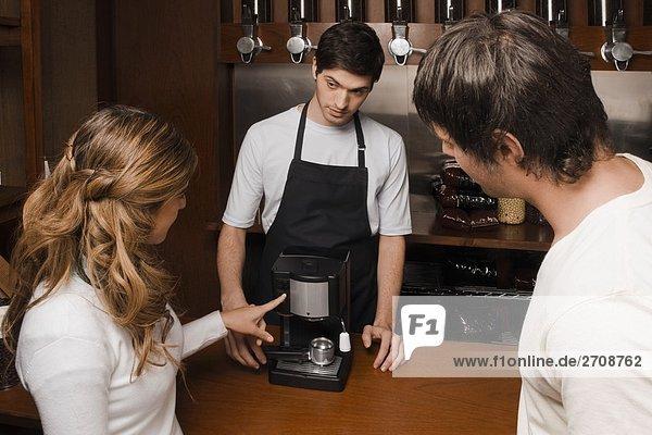 Coffee-Shop-Besitzer  die eine Kaffeemaschine zu Kunden
