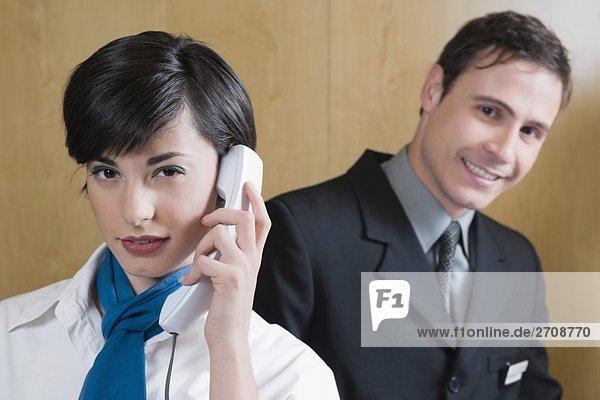 Nahaufnahme empfangsdame sprechen auf das Telefon und ein Geschäftsmann stehen hinter ihr