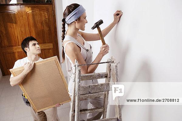 Junge Frau hämmern Nagel an der Wand mit einem jungen Mann hält einen Bilderrahmen