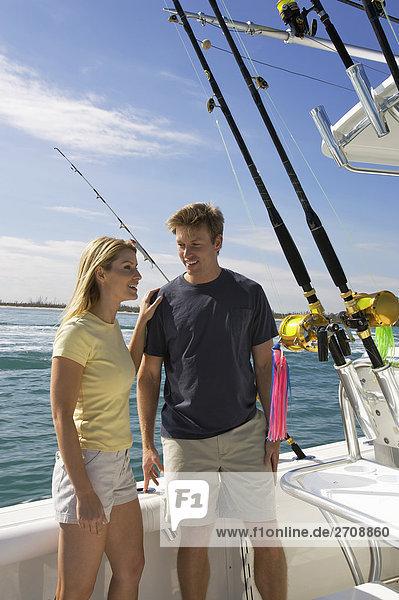 Mitte adult paar stehend auf ein Schnellboot und lächelnd