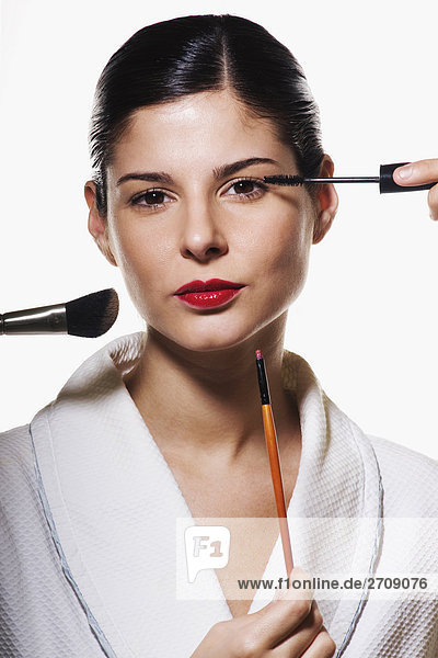 Portrait of a young woman applying make-up