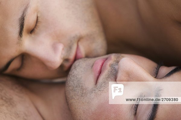 Portrait of a gay couple lying together