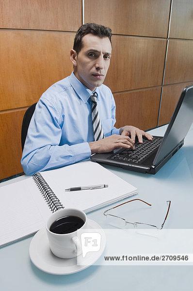 Portrait eines Kaufmanns auf einem Laptop in einem Büro arbeiten