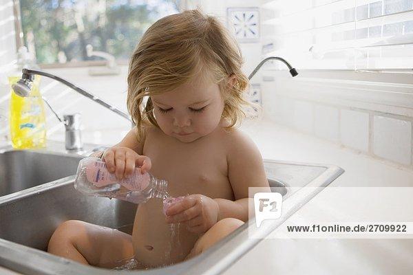 Nahaufnahme ein Babymädchen sitzen in das Waschbecken im Badezimmer