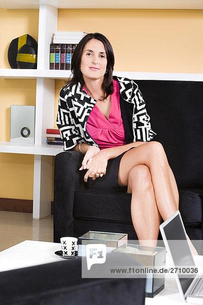 Portrait einer Mitte erwachsen frau sitzt auf einer couch