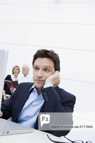 Mann gelangweilt am Tisch sitzend