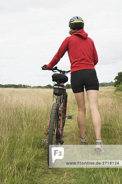 Radfahrerin schiebt Fahrradrückansicht