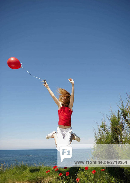 Junges Mädchen springt mit rotem Ballon