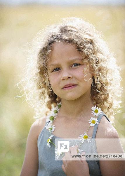 Junges Mädchen mit Gänseblümchenkette
