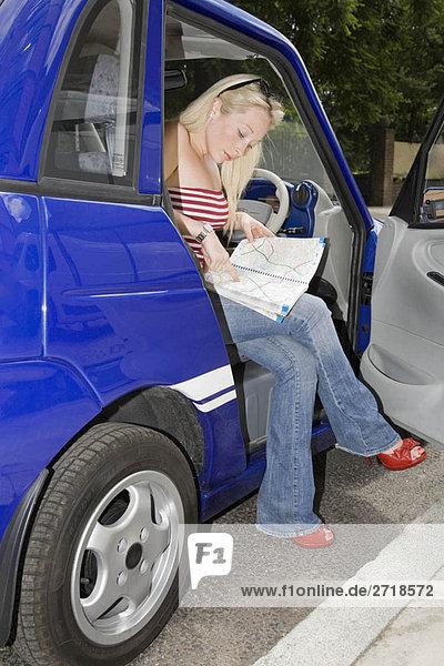 Junge Frau liest Karte im Elektroauto