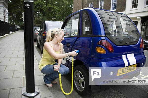 Junge Frau beim Aufladen eines Elektroautos