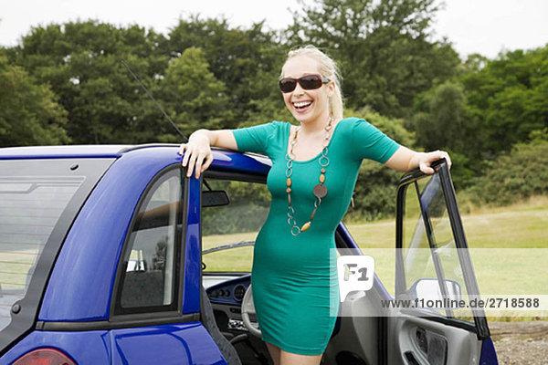 Junge Frau lächelt mit dem Elektroauto