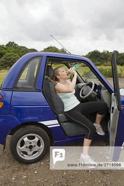 Junge Frau trinkt im Elektroauto