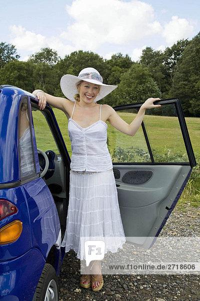 Junge Frau steht beim Elektroauto