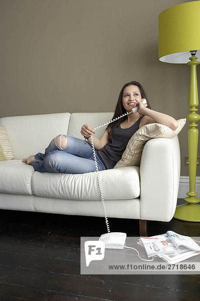 Frau auf dem Sofa mit Telefon