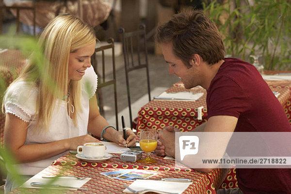 Paar Schreibpostkarten im Cafe