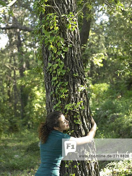 Junge Frau umarmt Baum