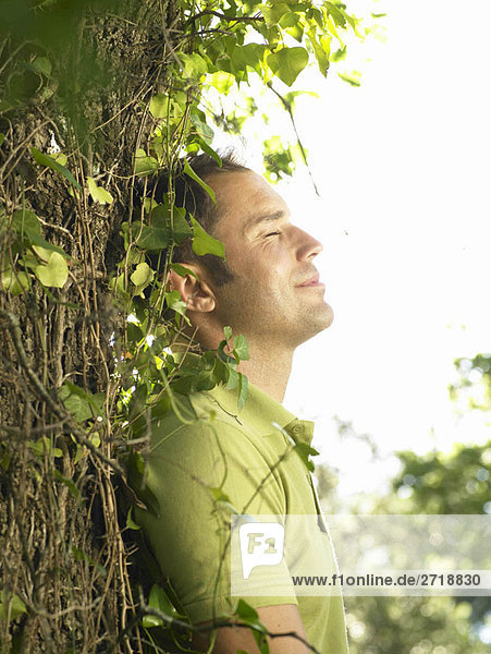 Junger Mann lehnt sich an den Baum
