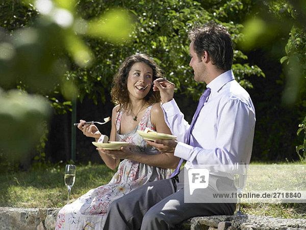 Hochzeitsgäste füttern sich gegenseitig Kuchen
