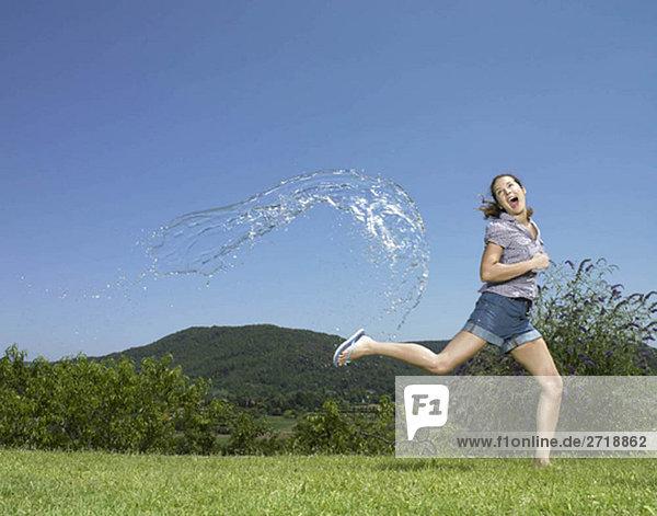 Mädchen läuft aus dem Wasserbogen