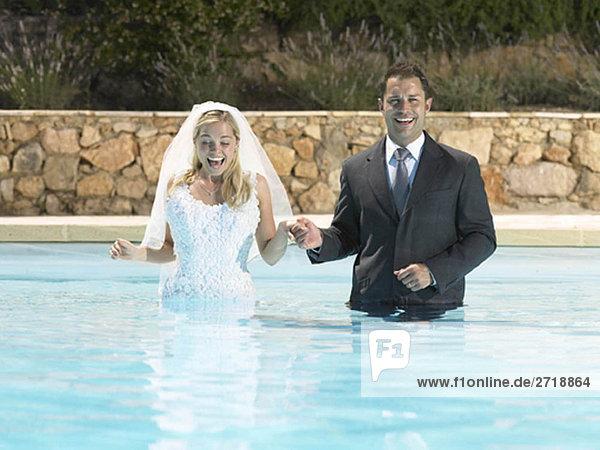 Braut und Bräutigam im Pool stehend