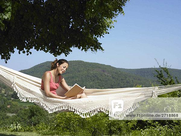 Mädchen beim Lesen in der Hängematte
