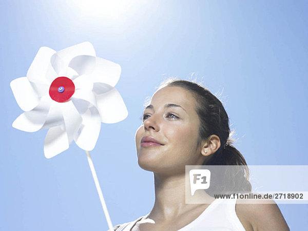 Mädchen hält Windmühle in der Sonne
