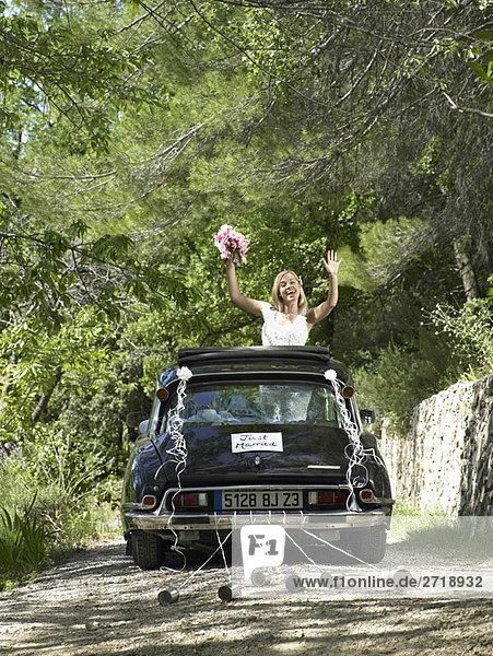 Braut winkt aus dem Hochzeitsauto