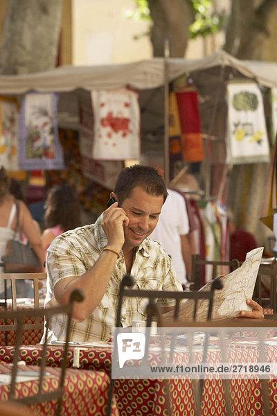 Mann am Telefon im französischen Cafe
