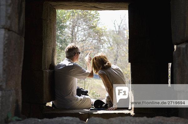 Paar sitzen im Fenster des Gebäudes Stein