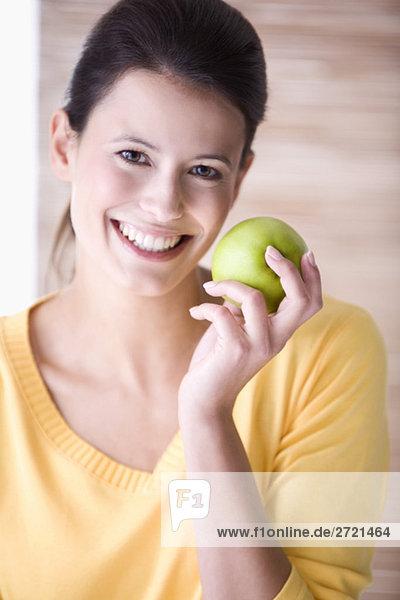 Junge Frau hält einen Apfel  lächelnd  Portrait
