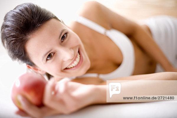Frau hält einen Apfel  lächelnd Frau hält einen Apfel, lächelnd