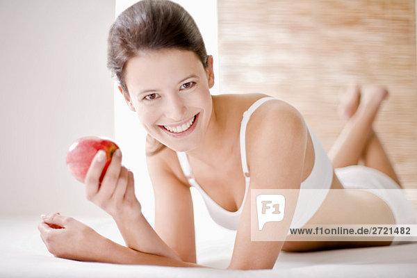 Junge Frau hält einen Apfel  lächelnd