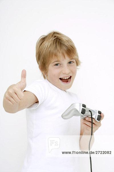 Junge (10-11) hält Spielkonsole mit Daumen hoch  Portrait  Nahaufnahme