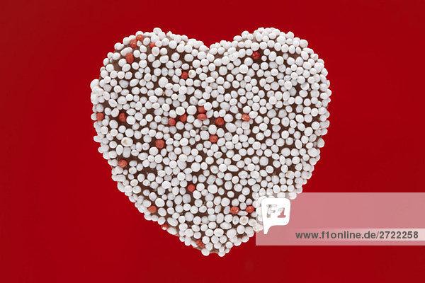 Schokoladenüberzogenes Herz mit Süßigkeitenstreuseln  Nahaufnahme