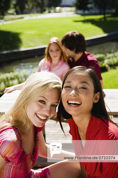 Upper   Two young women in beer garden  laughing  portrait