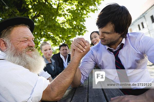 Obermaterial  zwei Männer im Biergarten-Armdrücken