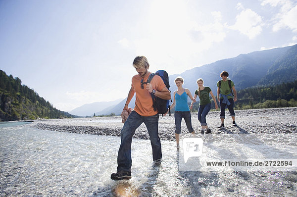 Germany  Bavaria  Tölzer Land  Young friends walking through river