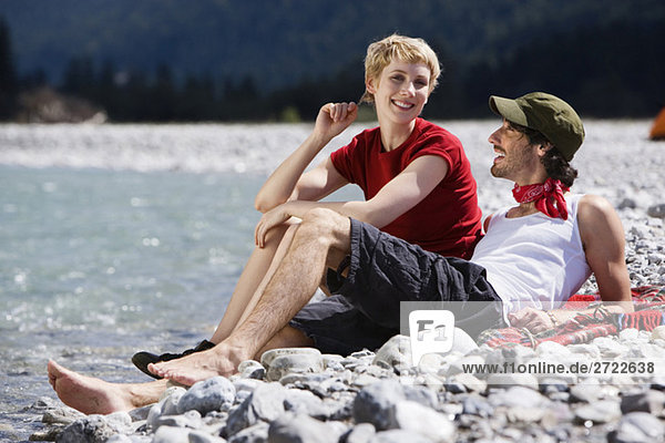 Germany  Bavaria  Tölzer Land  Young couple sitting by river