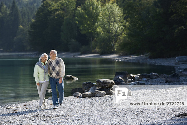 Germany  Bavaria  Walchensee  Senior couple walking across lakeshore