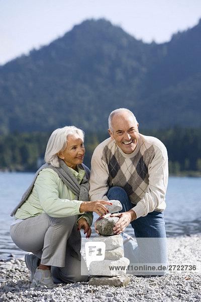 Germany  Bavaria  Walchensee  Senior couple piling up stones