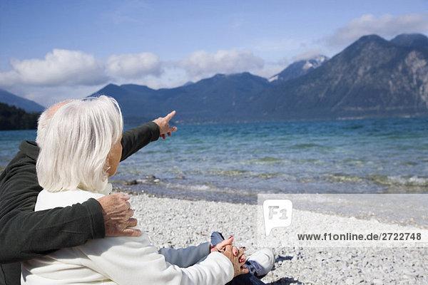 Deutschland  Bayern  Walchensee  Seniorenpaar am Seeufer  Rückansicht