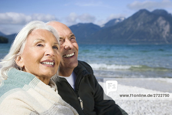 Germany  Bavaria  Walchensee  Senior couple relaxing on lakeshore