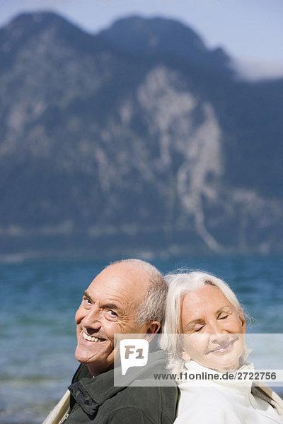Deutschland  Bayern  Seniorenpaar entspannt am Seeufer  Rücken an Rücken  lächelnd  Portrait