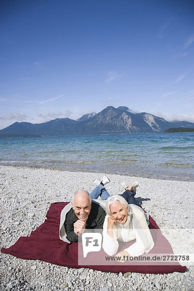 Germany  Bavaria  Walchensee  Senior couple relaxing on lakeshore