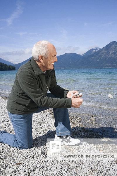 Senior man on lakeshore  about to skimming a stone