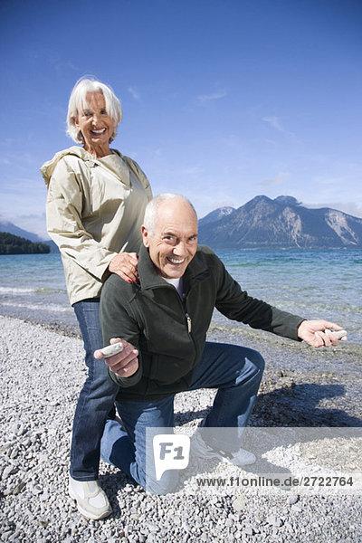 Deutschland  Bayern  Walchenseel  Seniorenpaar  das am Seeufer herumalbert