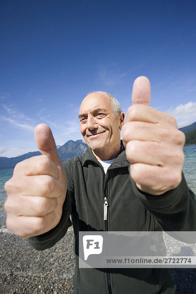 Senior Mann jubelt  Daumen hoch.