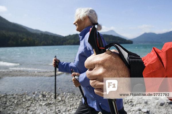 Deutschland  Bayern  Walchensee  Seniorenpaar  Nordic Walking am Seeufer