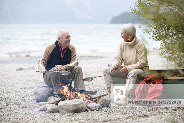 Germany,  Bavaria,  Walchensee,  Senior couple sitting at campfire,  grilling fish